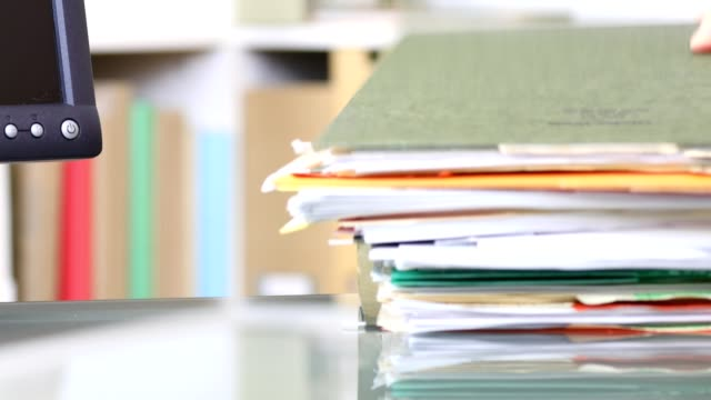stack of files, documents being piled onto office desk. - stack stock videos & royalty-free footage