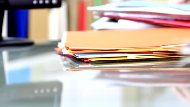 stack of files, documents being piled onto office desk. - file stock videos & royalty-free footage