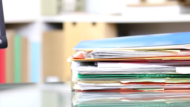 Stack of files, documents being piled onto office desk.