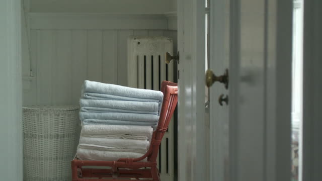 ms focusing stack of folded towels on chair in bathroom, scarborough, new york, usa - badezimmer stock-videos und b-roll-filmmaterial