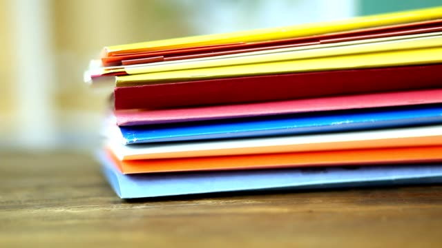 Stack of multi colored file folders on a desk in an office.