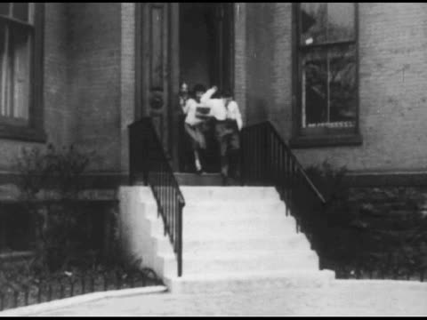 vídeos de stock, filmes e b-roll de / stack of museum flyers / children excitedly exit door / reverse shot of children running from exited building / empty stoop / interior room with... - 1951