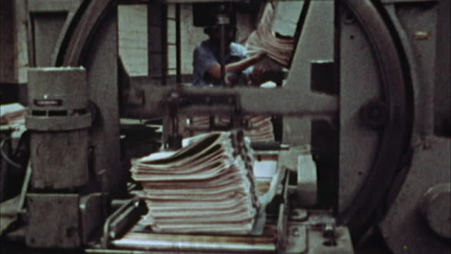 cu, pan, stack of newspapers being tied up in printing plant, 1970's, los angeles, california, usa - printing plant stock videos & royalty-free footage