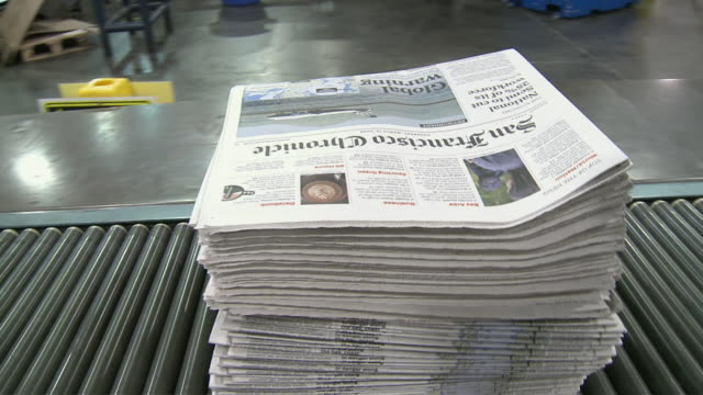 CU PAN Stack of newspapers on conveyor belt at printing plant, San Francisco, California, USA / AUDIO
