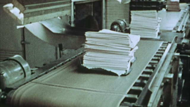cu, pan, stack of newspapers on conveyor in printing plant, 1970's, los angeles, california, usa - printing plant stock videos & royalty-free footage