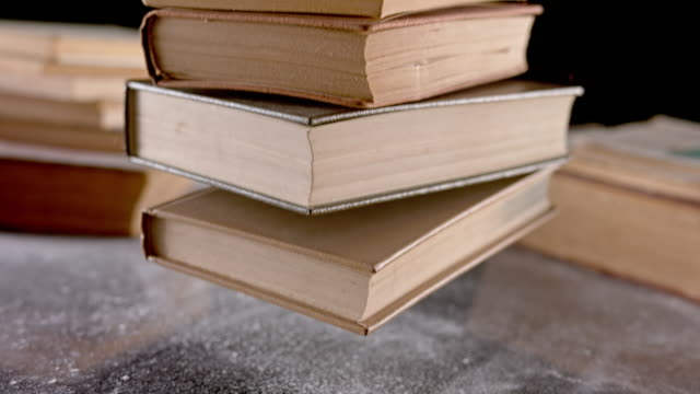 vídeos de stock e filmes b-roll de slo mo stack of old books falling onto a table - literatura
