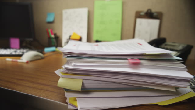 Stack of paperwork is dropped on an office desk.