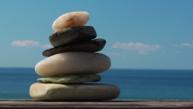 CU, Stack of pebbles in jar on wooden railing, ocean in background, North Truro, Massachusetts, USA