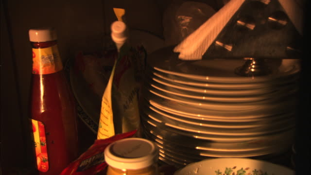 a stack of plates, condiments and a napkin holder rattle in a boat's galley. - condiments stock videos and b-roll footage