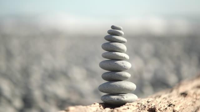 vidéos et rushes de pile de roches équilibrant sur la plage. - sans mise au point and équilibre