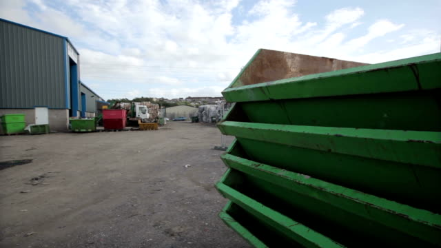 stockvideo's en b-roll-footage met stack of skips and truck at a recycling centre - afvalcontainer container