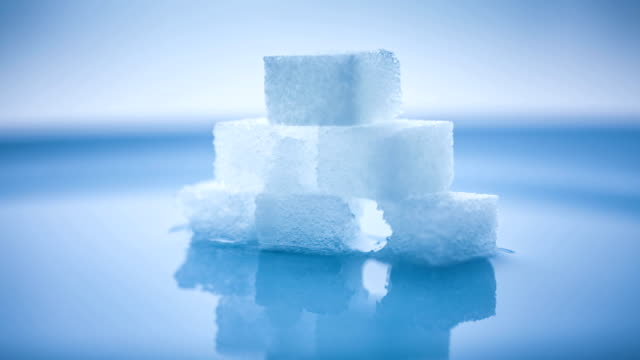 t/l stack of sugarcubes dissolving in water - sugar cube stock videos & royalty-free footage