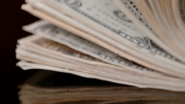 Stack of US currency on black background, super slow motion
