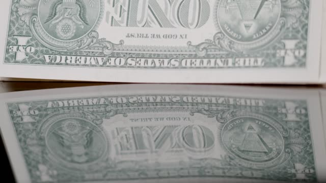 Stack of US currency one dollar bills falling on black background, super slow motion