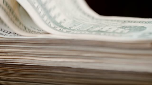 Stack of US currency twenty dollar bills falling on black background, super slow motion