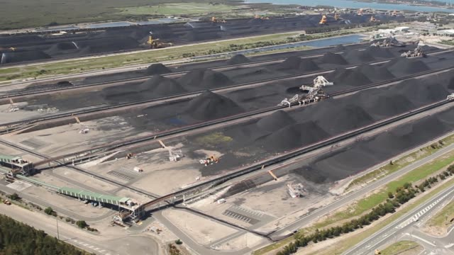Stacker reclaimers operate next to stockpiles of coal at the Newcastle Coal Terminal in this aerial video taken in Newcastle north of Sydney...