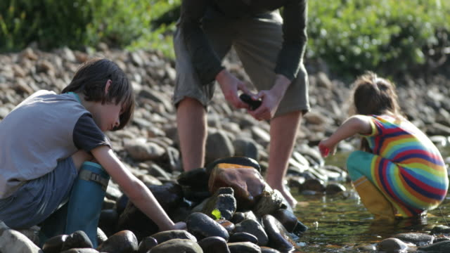 stacking rocks in the river - riverbank stock videos & royalty-free footage