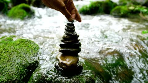 vidéos et rushes de empilement de pierres zen dans la nature - bouddhisme