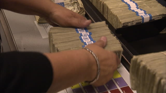 CU ZO Stacks of 1 dollar bills placing on conveyor belt / Kansas City, Kansas, United States