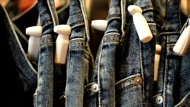 vídeos de stock e filmes b-roll de stacks of new blue jeans in the store - jeans