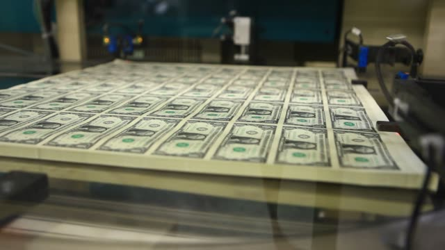 stacks of one dollar note sheets pass through a kbanotasys sa large printing machine after receiving a serial number and the us treasury and us... - 米国ドル紙幣点の映像素材/bロール