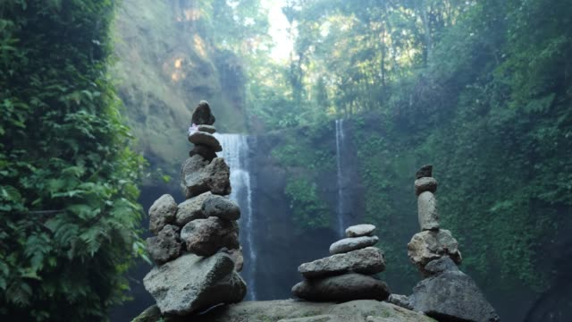 stacks of rocks with waterfall in background - balance stock videos and b-roll footage