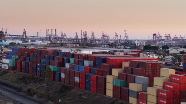 vídeos de stock e filmes b-roll de stacks of shipping containers in an intermodal yard - drone shot - wilmington cidade de los angeles