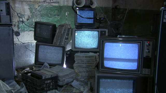 MS Stacks of televisions tuned to static, surrounded by bundles of newspaper and a crate of records/ Los Angeles, California