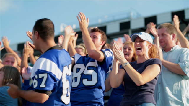 Stadium crowd cheers at football game, various high-fives