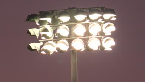 vídeos y material grabado en eventos de stock de stadium floodlight lighting lights at a night football game, friday night lights, american football. - slow motion - reflector luz eléctrica