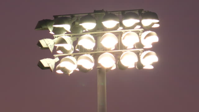 stadium floodlight lighting lights at a night football game, friday night lights, american football. - slow motion - floodlight stock videos & royalty-free footage