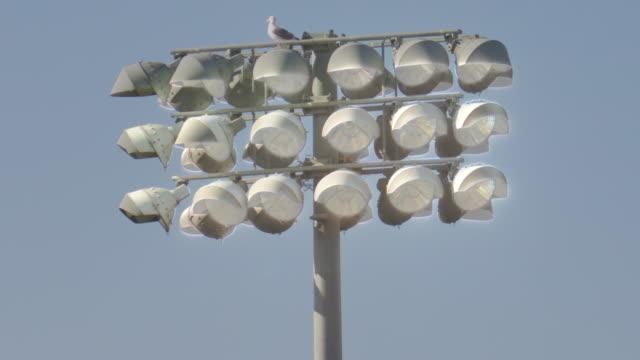 stadium floodlight lighting lights at a night football game, friday night lights, american football. - slow motion - match lighting equipment stock videos & royalty-free footage