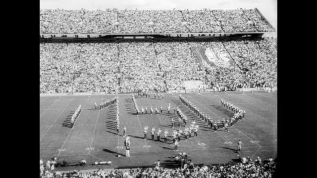 / stadium full of cheering fans and college band and cheerleaders on the field / coach clarence lester 'biggie' munn introduces actor from spartacus... - 1950 1959 stock-videos und b-roll-filmmaterial