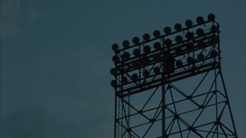 vídeos y material grabado en eventos de stock de stadium lights on a tower illuminate. - reflector luz eléctrica