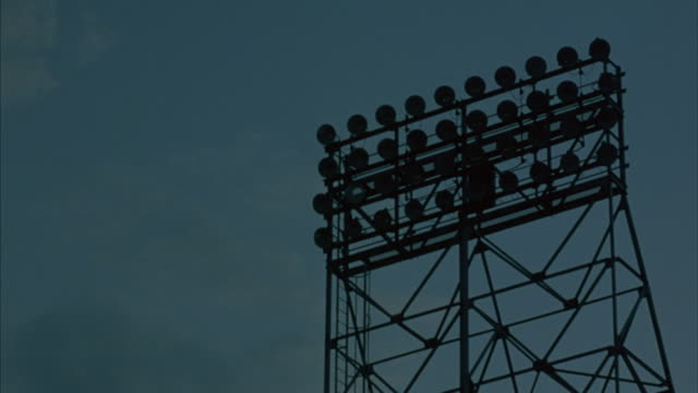 stadium lights on a tower illuminate. - floodlight stock videos & royalty-free footage