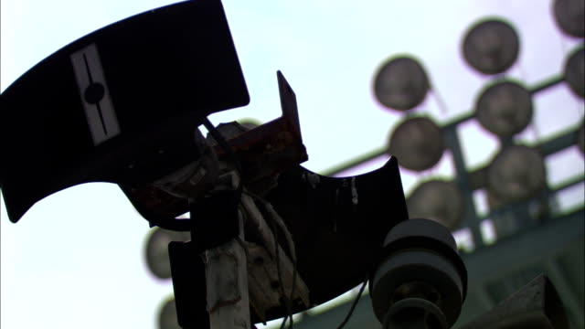 stadium lights tower over a loudspeaker and microphone at a football field. - microphone stock videos & royalty-free footage