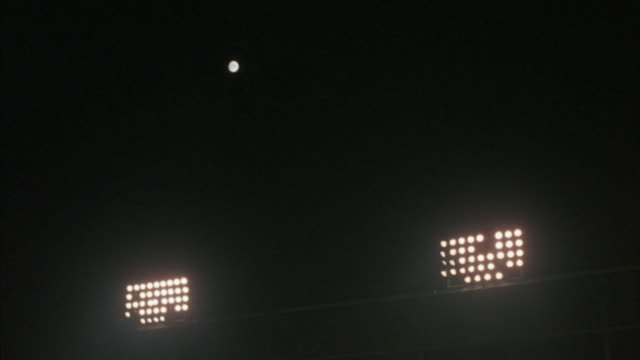 stadium lights turn on at night. - floodlight stock videos & royalty-free footage