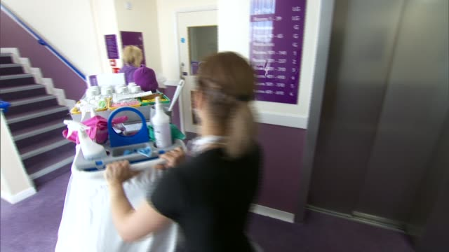 staff and customers at premier inn hotel int staff working at reception desk / various of housekeeper and chamber maids cleaning and preparing hotel... - inn stock videos & royalty-free footage