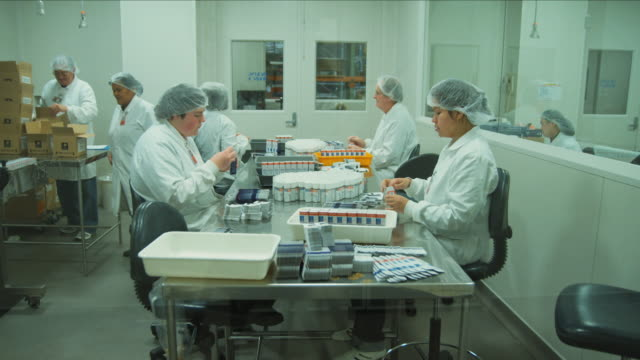 t/l ws staff at pharmaceutical company putting restricted pill bottles in boxes manually / auckland, new zealand - pharmaceutical manufacturing machine stock videos & royalty-free footage