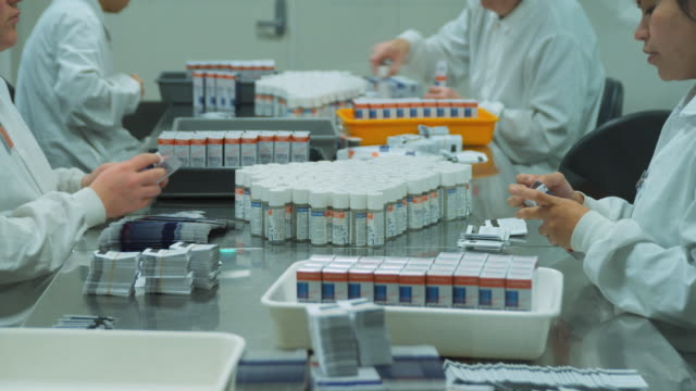 t/l ms staff at pharmaceutical company putting restricted pill bottles in boxes manually / auckland, new zealand - medikament stock-videos und b-roll-filmmaterial