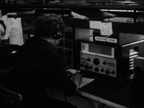 staff at the bbc's monitoring service listen to russian radio broadcasts on yuri gagarin's space flight - trasmissione radiofonica video stock e b–roll