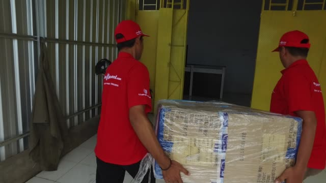 vidéos et rushes de a staff checks newlyarrivedboxes at lion parcel facility in makassar south sulawesi province indonesia on friday march 11 2016 shots tracking footage... - post it