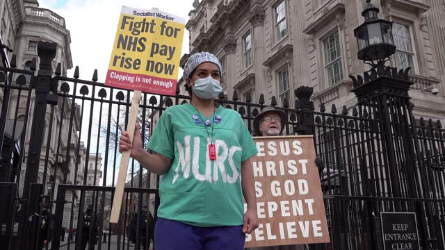 staff hold banners and placards outside downing street on a protest demanding a better pay rise than the 1% announced by chancellor rishi sunak... - paying stock videos & royalty-free footage