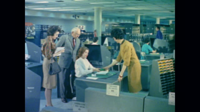 1962 staff look up social security information on confidential microfilm records - servizio sociale video stock e b–roll