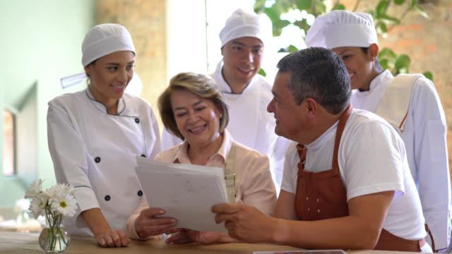 Personeelsvergadering met de manager; chef-kok; seus chef-koks en ober