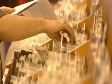 vídeos y material grabado en eventos de stock de staff member sorts through cd racks in music shop - gran almacén