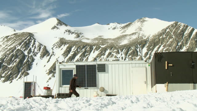 ws of ale staff member walking into weather station cabin with snowy mountains / union glacier, heritage range, ellsworth mountains, antarctica  - wetterstation stock-videos und b-roll-filmmaterial