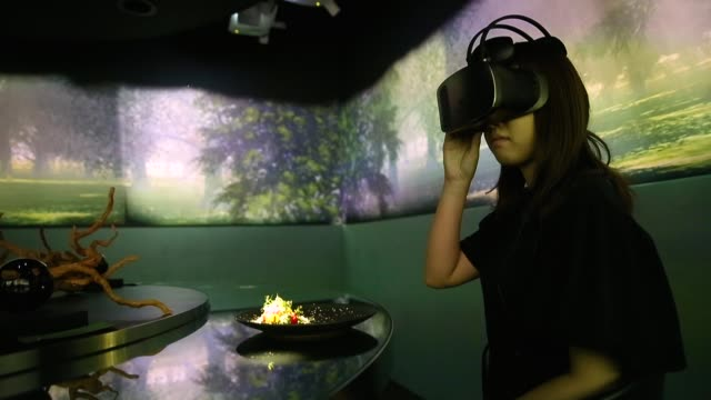 stockvideo's en b-roll-footage met a staff member wears a virtualreality headset as the 'spur' dish is served during a demonstration in the main dining room of the tree by naked yoyogi... - dining room