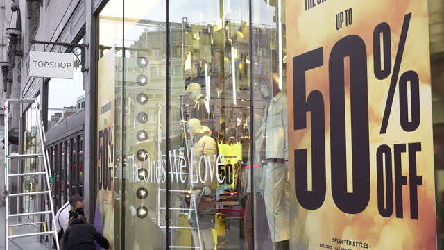 staff members put up 50 percent off sales posters at the top shop store on oxford street on the first morning the new covid regulation three tier... - turning on or off stock videos & royalty-free footage