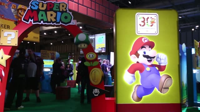 Staff members walk past a Super Mario logo at a Nintendo Co Ltd stand at the EGX 2015 video gaming conference in Birmingham UK on Thursday Sept 24...